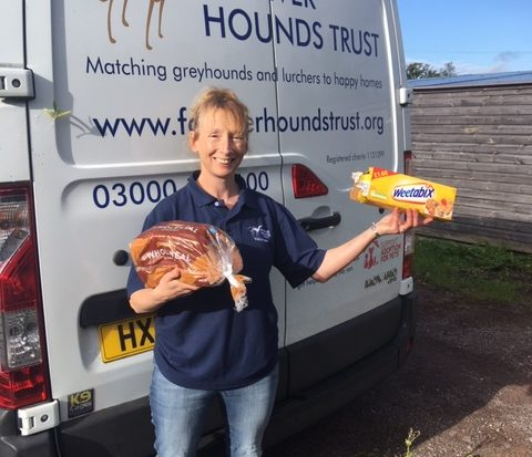 Forever Hounds Trust volunteer in front of the Forever Hounds Trust van with a box of Weetabix and a loaf of bread