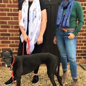 Two ladies wearing greyhound scarves and black greyhound
